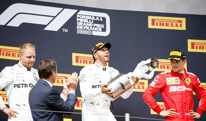 Mercedes driver Lewis Hamilton celebrates on the podium after winning the French Grand Prix, alongside second-placed Mercedes's Valtteri Bottas and third-placed Ferrari's Charles Leclerc
