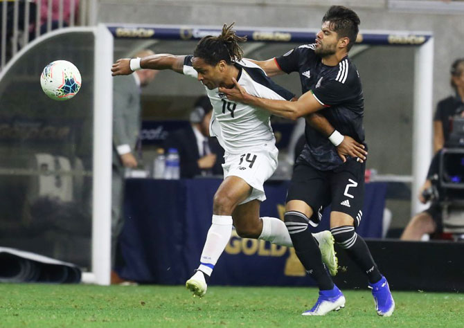 Costa Rica forward Jonathan Mc Donald (14) is grabbed by Mexico defender Nestor Araujo (2) as they vie for possession in the second half of the quarter-final in the CONCACAF Gold Cup soccer tournament at NRG Stadium in Houston, Texas on Saturday