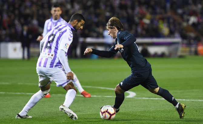 Real Madrid's Luka Modric dribbles past Real Valladolid's Borja Fernandez