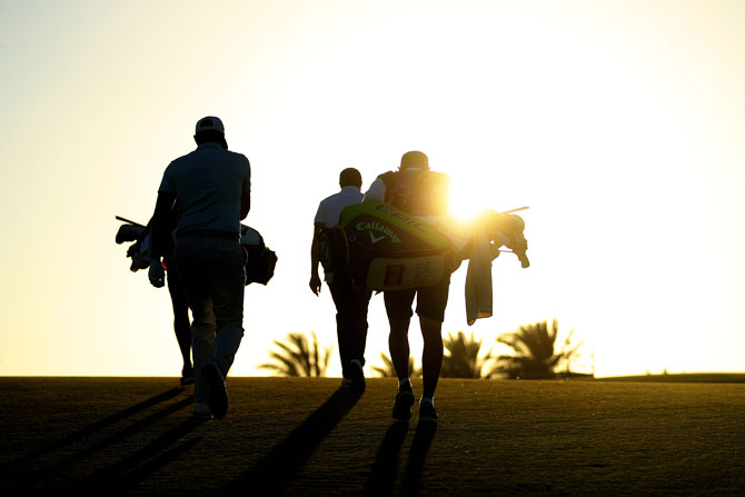 Players and caddies walk along the 7th hole as the sun sets during day two of the Commercial Bank Qatar Masters at Doha GC in Doha, Qatar, on Friday, March 8