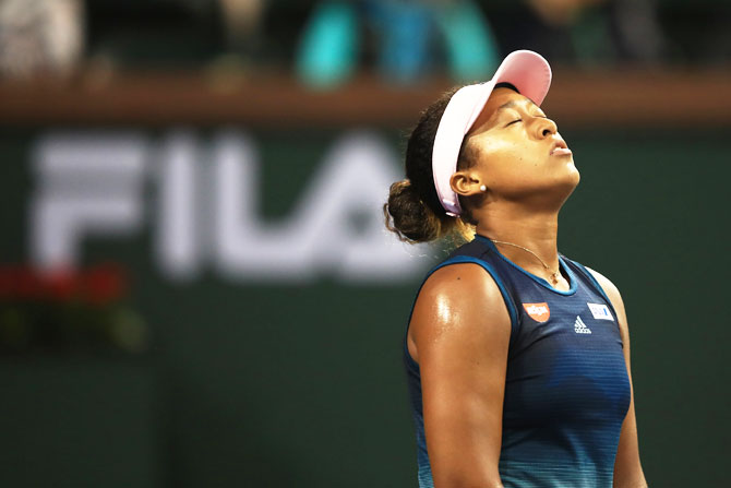 Japa's Naomi Osaka reacts during her loss to Switzerland's Belinda Bencic on Day 9  of the BNP Paribas Open at the Indian Wells Tennis Garden in Indian Wells, California, on Tuesday