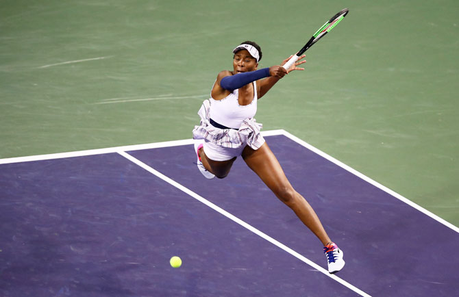 USA's Venus Williams plays a forehand against Germany's Mona Barthel during their women's singles fourth round match