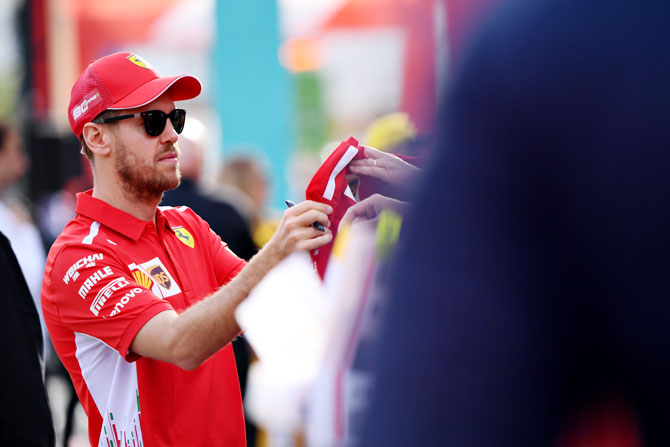 Ferrari's German driver Sebastian Vettel signs autographs for fans at the F1 Live event during previews ahead of the F1 Grand Prix of Australia at Melbourne Grand Prix Circuit in Melbourne on Wednesday