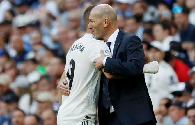 Real Madrid's Karim Benzema is embraced by coach Zinedine Zidane after being substituted off during their La Liga match against Celta Vigo at Santiago Bernabeu in Madrid on Saturday