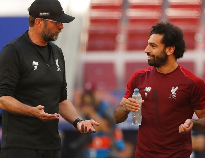 Liverpool manager Juergen Klopp talks with Mohamed Salah during training