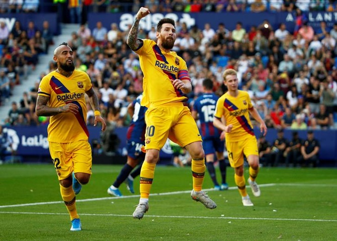 Lionel Messi celebrates putting Barcelona ahead from the penalty spot against Levante.
