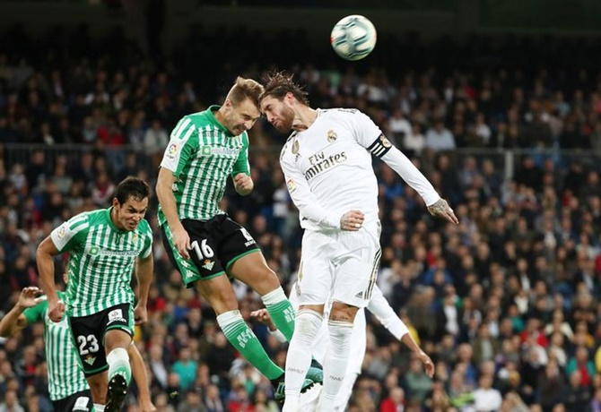 Real Madrid's Sergio Ramos and Real Betis's Loren battle for an aerial ball.