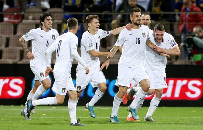 Francesco Acerbi celebrates scoring Italy's first goal with Andrea Belotti and teammates.