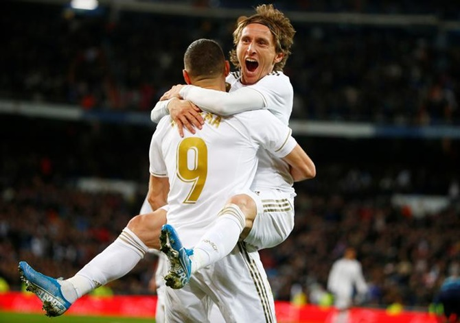 Luka Modric celebrates scoring Real Madrid's third goal with Karim Benzema in Saturday's La Liga match against Real Sociedad