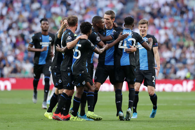 Club Brugge's Emmanuel Bonaventure Dennis celebrates with teammates after scoring his team's first goal against Real Madrid during their UEFA Champions League Group A match at Santiago Bernabeu in Madrid on Tuesday