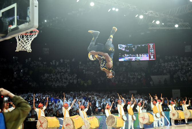 A member of the Indiana Pacers Powerpack performs a dunk off a trampoline, at the half-time show, during the during the NBA pre-season game played between Sacramento Kings and Indiana Pacers in Mumbai on Friday