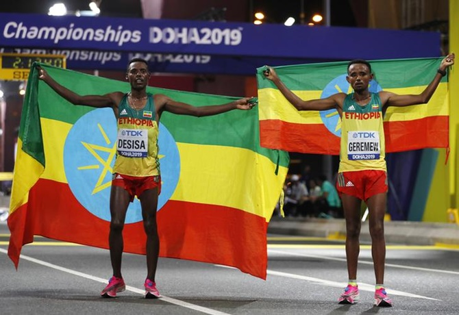 Ethiopia's Lelisa Desisa poses with countryman Mosinet Geremew as he celebrates winning gold after a 1-2 finish in the men's marathon at the World Athletics Championships, in Doha, on Sunday.