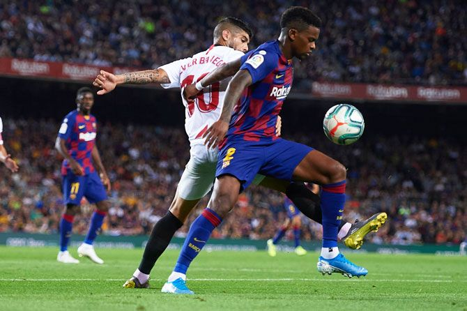 Sevilla FC's Ever Banega (L) competes for the ball with FC Barcelona's Nelson Semedo