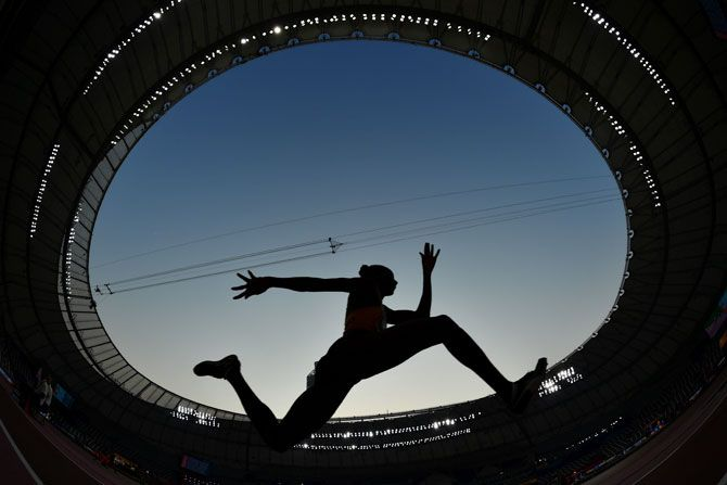 An athlete competes during the women's triple jump qualification