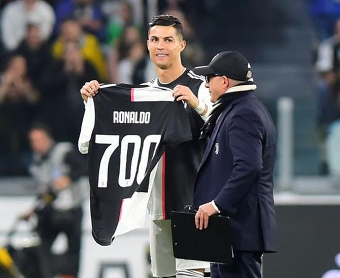 Juventus's Cristiano Ronaldo holds up a shirt to commemorate his 700 career goals before the match against Bologna.
