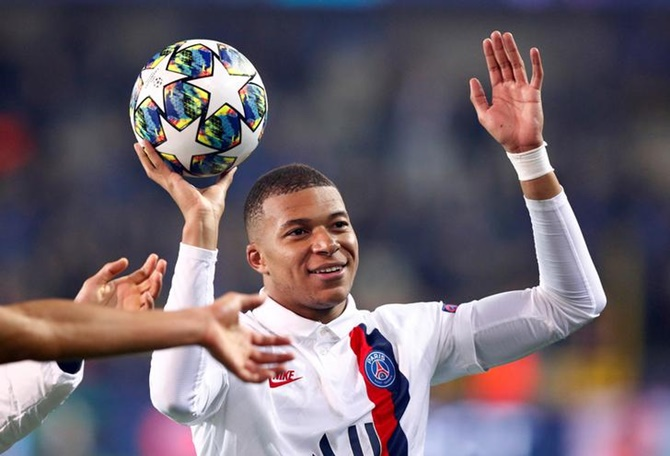 Kylian Mbappe celebrates after with the ball after Paris St Germain's victory over Club Brugge in the Champions League Group A match