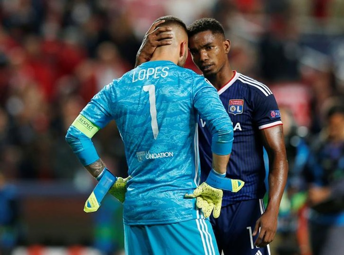 Olympique Lyonnais goalkeeper Anthony Lopes is consoled by teammate Thiago Mendes after the Group G match against Benfica