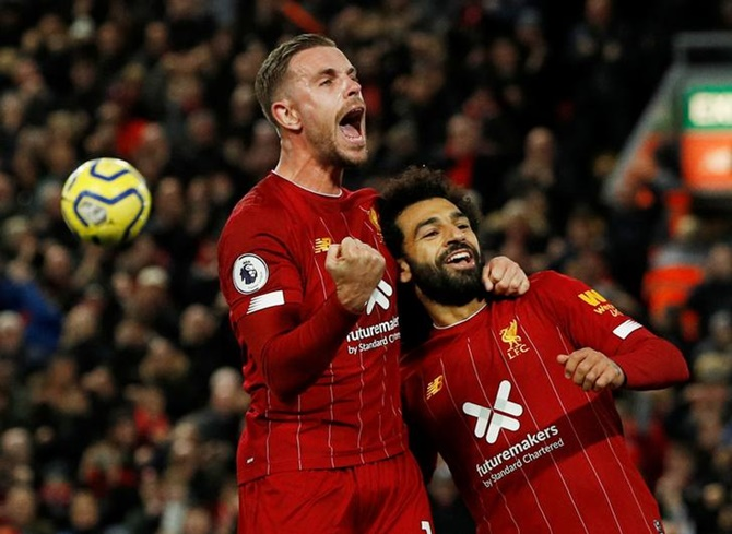 Mohamed Salah celebrates scoring Liverpool's second goal with Jordan Henderson during Sunday's Premier League match against Tottenham Hotspur