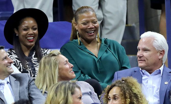 Hollywood actress Queen Latifah, right, shares a laugh with friends, while the she attends the match between Serena Williams and Wang Qiang