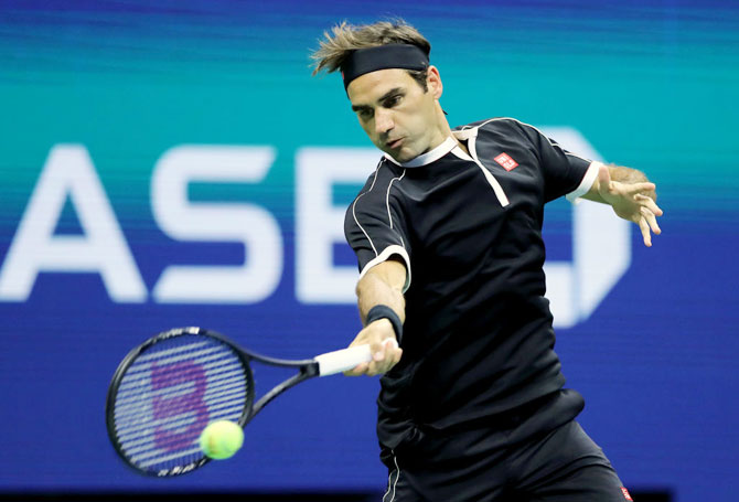 Roger Federer returns a shot against Grigor Dimitrov