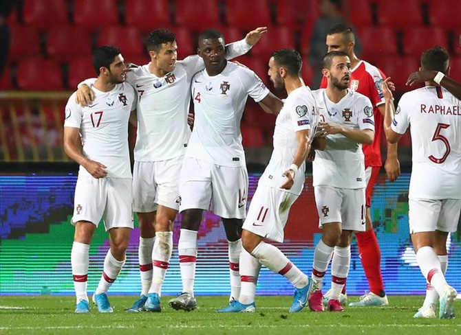 William Carvalho celebrates with Cristiano Ronaldo and teammates after scoring Portugal's first goal in the Euro 2020 Group B Qualifier against Serbia in Belgrade.