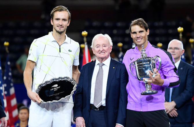 Rafael Nadal of Spain (right) and Daniil Medvedev of Russia (left) hold their trophies while posing with Rod Laver after the US Open final on Sunday