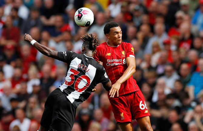 Newcastle United's Christian Atsu and with Liverpool's Trent Alexander-Arnold in an aerial battle