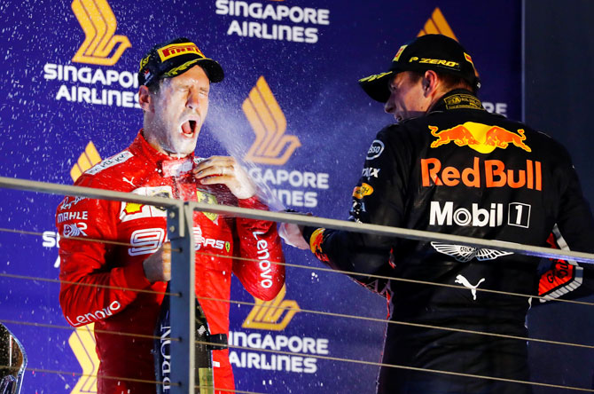 Race winner Ferrari's Sebastian Vettel is sprayed in the face with sparkling wine by third placed Red Bull's Max Verstappen as they celebrate on the podium