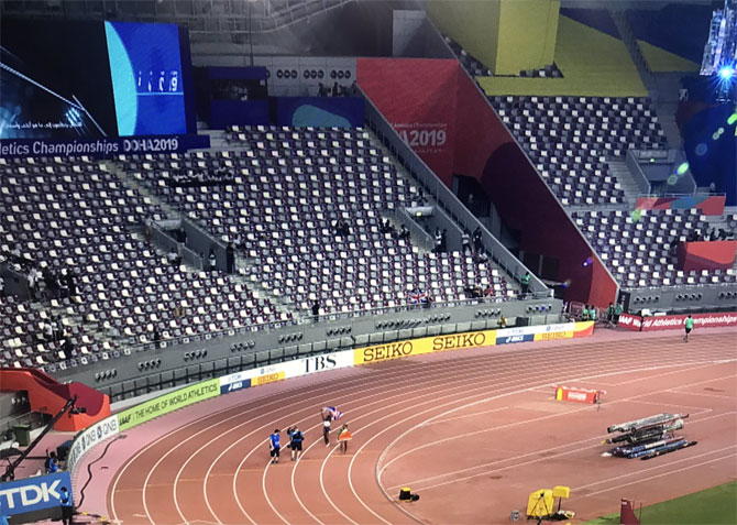 An athlete takes a lap of honour in front of a near-empty stand