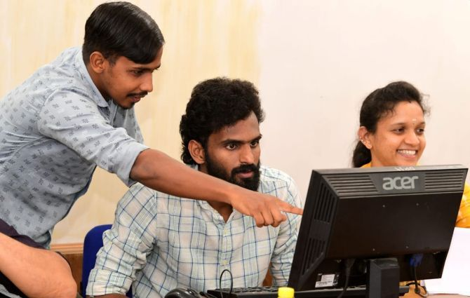 India and Jamshedpur FC footballer CK Vineeth (right) with a co-worker at a government helpline centre