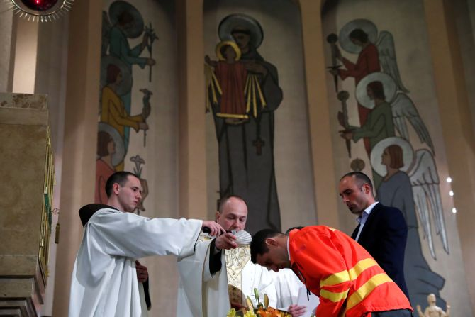 A Franciscan priest baptizes triathlon champion Akos Vanek as a gesture to honor his voluntary service as a paramedic during Easter Saturday service amid the coronavirus disease (COVID-19) outbreak in Budapest, Hungary, on April 11