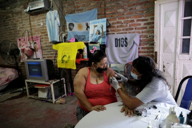 Cintia Veronica, a devoted Diego Maradona fan, gets an image of Maradona tattooed on her arm at her home in Buenos Aires