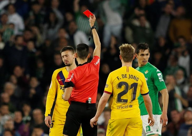 Barcelona's Clement Lenglet is shown a red card by referee Sanchez Martinez during Sunday's La Liga match against  Real Betis.