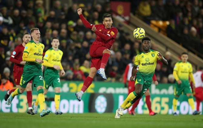 Liverpool's Roberto Firmino breaks through the Norwich defence and shoots at goal.