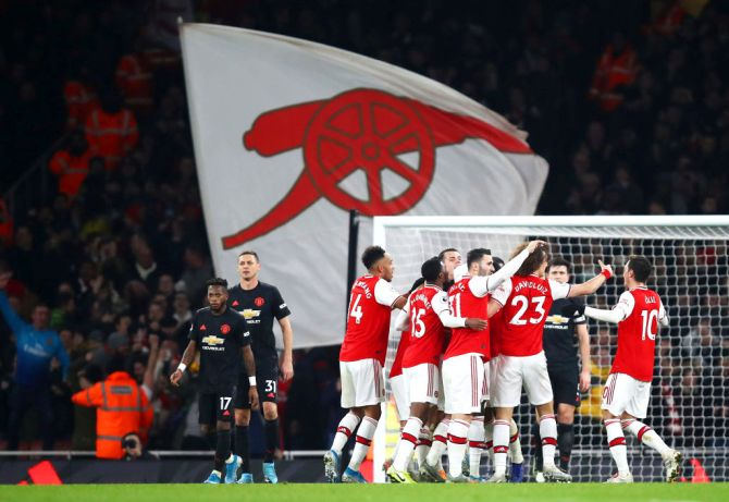 Arsenal's Sokratis Papastathopoulos celebrates with his teammates after scoring his team's second goal against Manchester United at Emirates Stadium in London on Thursday