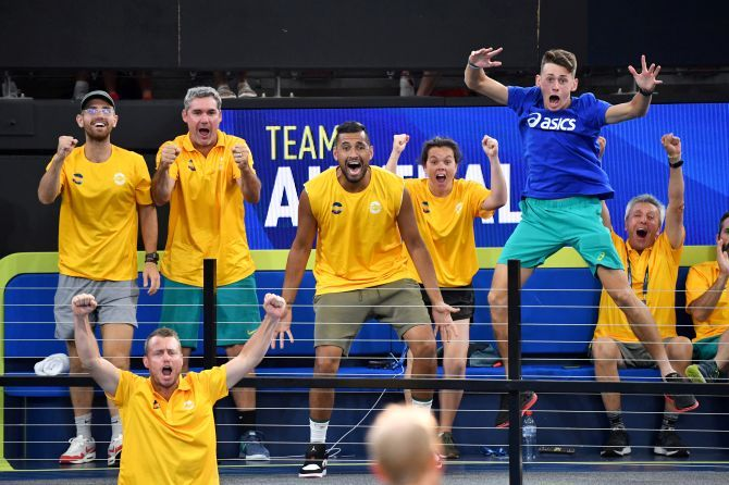 Team Australia players Nick Kyrgios and Alex de Minaur are seen celebrating as their team mates Chris Guccione and John Peers play their doubles match against Felix Auger-Aliassime and Adil Shamasdin of Canada during day 3 of the ATP Cup tennis tournament at Pat Rafter Arena in Brisbane, Australia, on Sunday