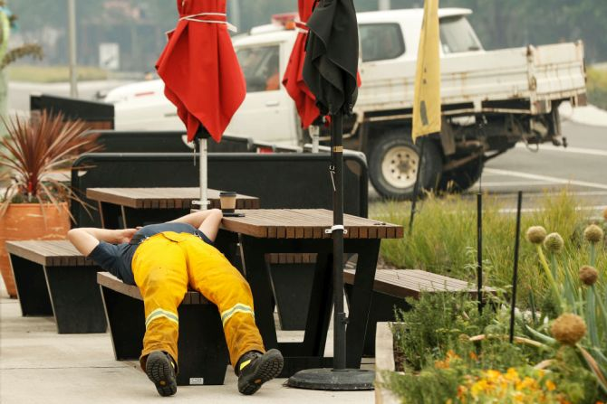 A tired firefighter rests outside a cafe in Cann River, Australia, on Monday. Milder weather conditions have provided some relief for firefighters in Victoria as bushfires continue to burn across the East Gippsland area, as clean up operation and evacuations continue. Two people have been confirmed dead and four remain missing. More than 923,000 hectares have been burnt across Victoria, with hundreds of homes and properties destroyed. 14 people have died in the fires in NSW, Victoria and South Australia since New Year's Eve