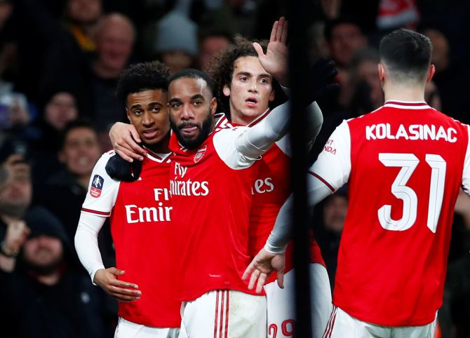 Arsenal's Reiss Nelson celebrates with teammates Alexandre Lacazette, Matteo Guendouzi and Sead Kolasinac after scoring their first goal  against Leeds United in their FA Cup third round match at Emirates Stadium in London on Monday