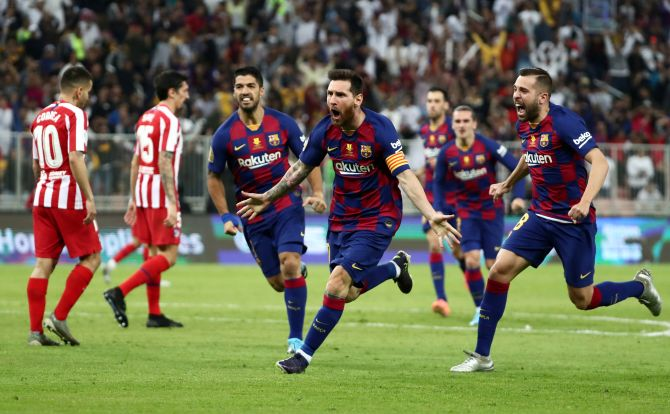 Barcelona's Lionel Messi celebrates with Jordi Alba and Luis Suarez after scoring their first goal against Atletico Madrid