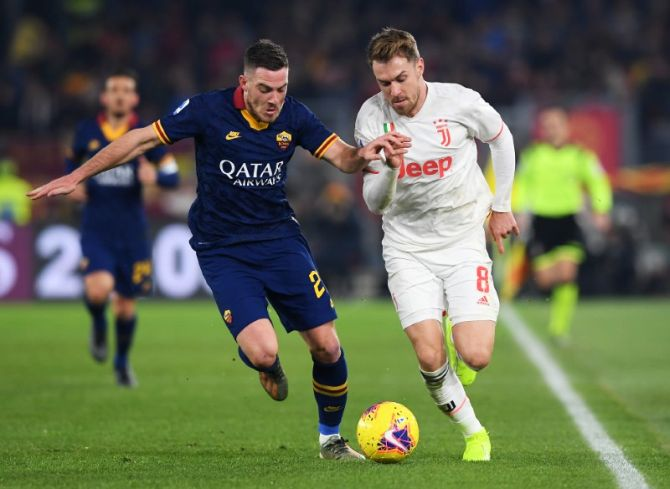 Juventus' Aaron Ramsey in action and AS Roma's Jordan Veretout vie for possession