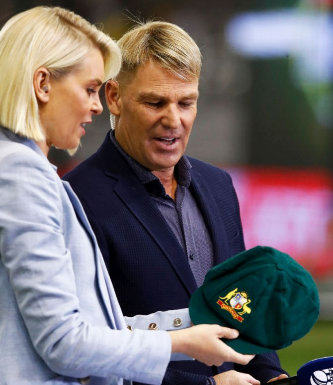 Fox Sports commentator Sarah Jones and Shane Warne, with his baggy green cap which was sold for more than $1 million, with all funds going to the bushfire appeal, ahead of the Big Bash League match between the Melbourne Renegades and the Melbourne Stars at Marvel Stadium in Melbourne on Friday
