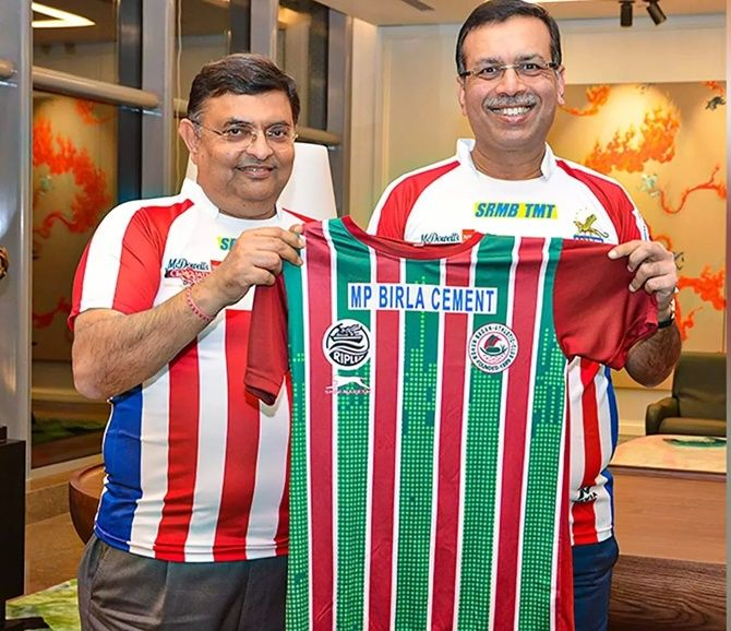 RPSG Group chairman Sanjiv Goenka, right, displays a jersey at the Mohun Bagan-ATK merger on Thursday