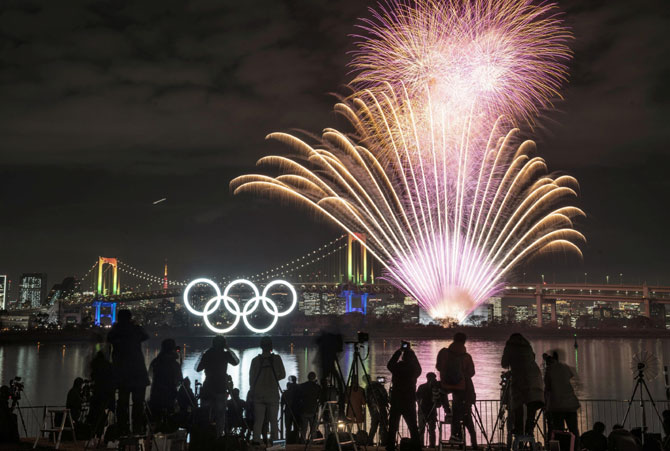 Fireworks light up the sky near the illuminated Olympic rings at a ceremony to mark six months before the start of the 2020 Olympic Games in Tokyo.