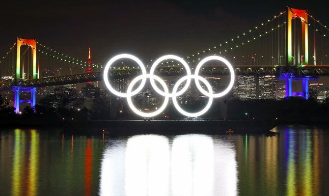 A giant monument of the five interlocking Olympic rings lit up, nestled in the water at Odaiba Marine Park in Tokyo Bay