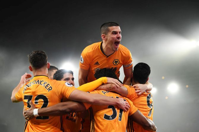 Wolverhampton Wanderers' Conor Coady jumps on his teammates as they celebrate Raul Jimenez's goal