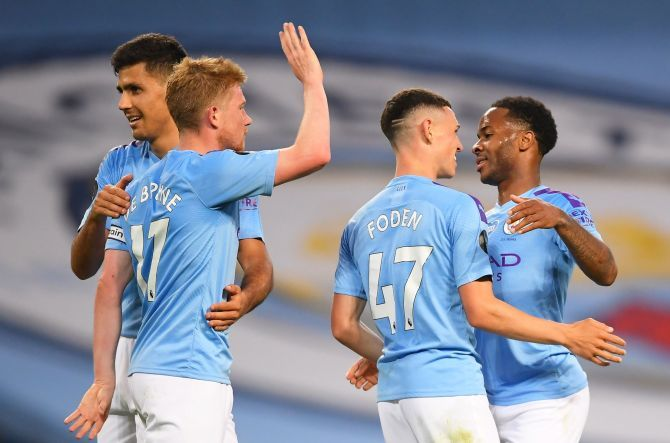 Manchester City's Raheem Sterling celebrates scoring their fourth goal with teammates at the Etihad Stadium in Manchester