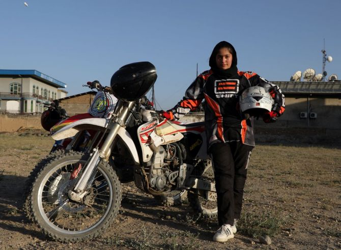 Wearing a white helmet and black and red motorbike suit, she trains with male riders on a barren lot surrounded by warehouses and private homes.