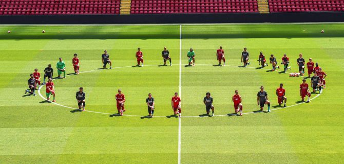 Liverpool FC players take a knee before their training session on Monday