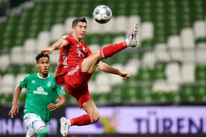 Bayern Munich's Robert Lewandowski goes airborne as he gets possession
