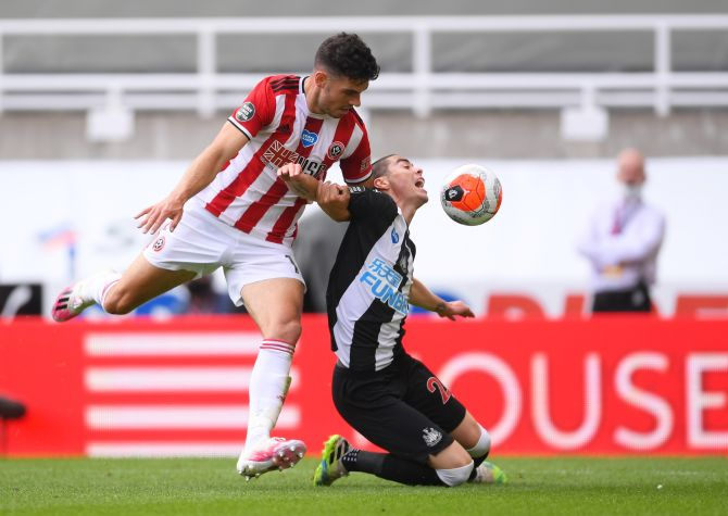 Sheffield United's John Egan in action with Newcastle United's Miguel Almiron